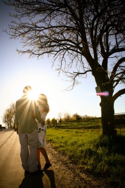 sun flare vermont engagement portrait taken along road with big tree