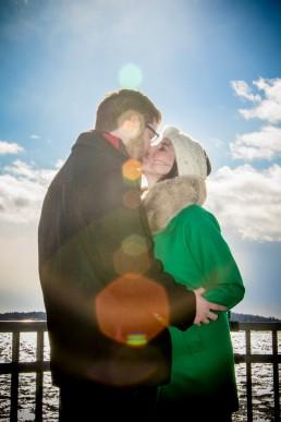 sun flare kiss engagement portrait on lake champlain in winter