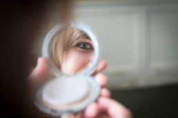 Bride getting ready with eye reflected in mirror near Rutland, Vermont