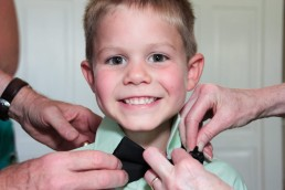 Adorable wedding ring bearer boy getting ready with bow tie in Woodstock, Vermont