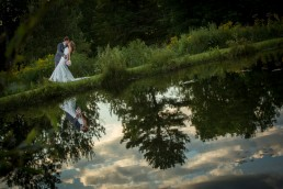 Wedding portrait of couple dipping, reflected in water at the Alerin Barn in Vermont