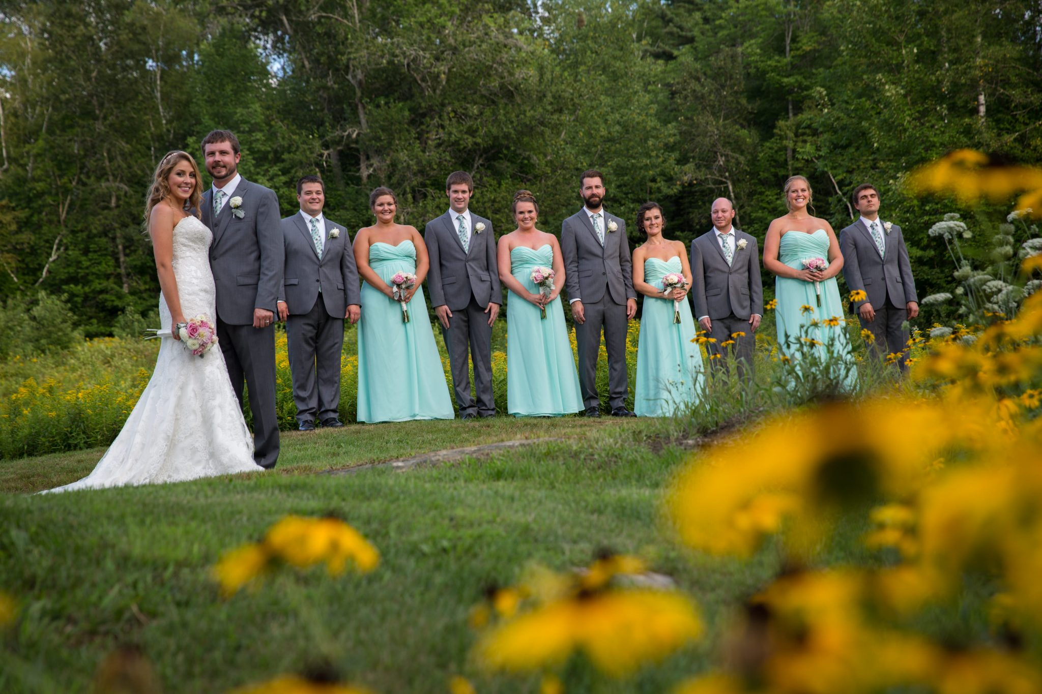 Wedding party portrait among flowers captured at the Alerin Barn in Vermont