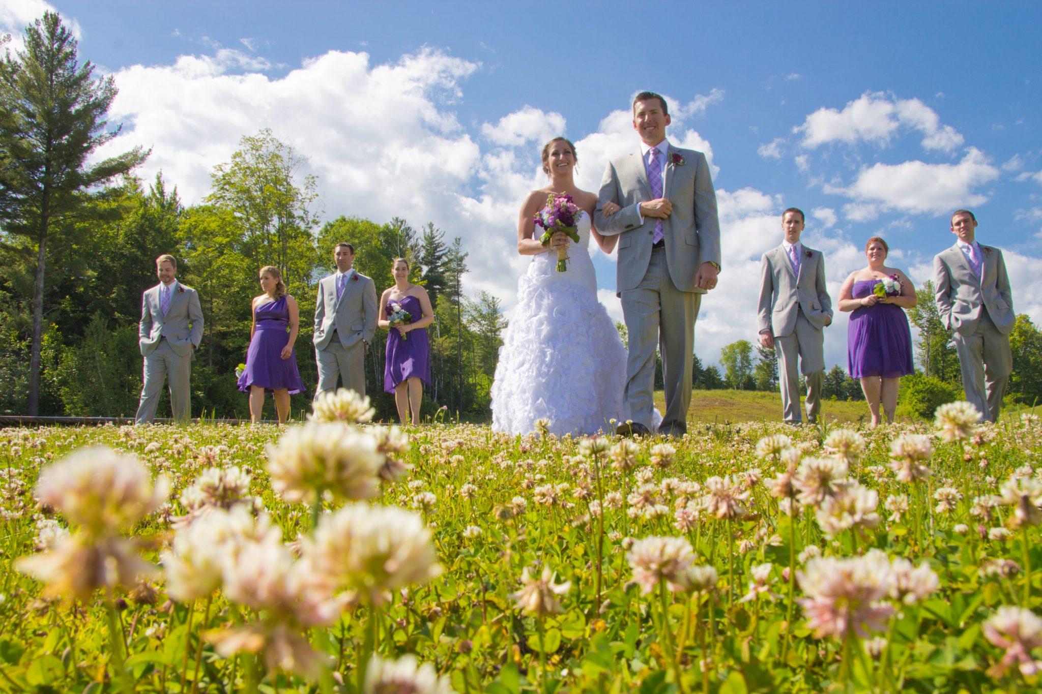 Wedding party portrait walking through flower field in Okemo, Vermont