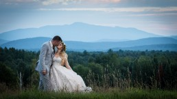 Wedding portrait kiss with mountains in background at Grace Farm in Saint Albans, Vermont