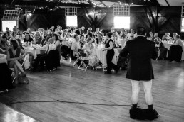 Black and white image of pants off at wedding reception toast at the Iron Lantern in Vermont